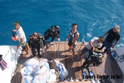 Дайверы возвращаются на борт, с мусором